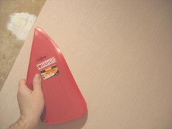 разглаживание обоев пластмассовым шпателем